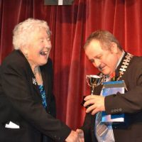 Stella Harvey being presented with her trophy by Town Mayor Brian Clemens